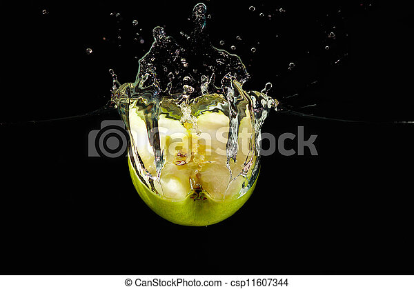 Halved green apple falling into the water with a splash on black background