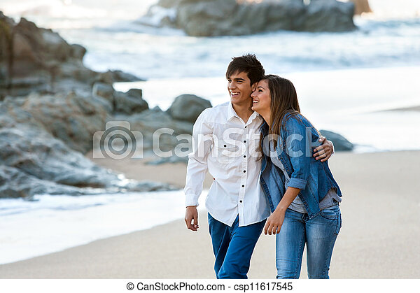 Cute teen couple walking along beach. - csp11617545