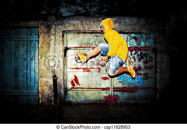 Young man jumping on grunge wall - csp11628953