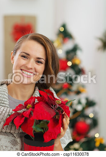 Happy woman holding Christmas rose in front of Christmas tree