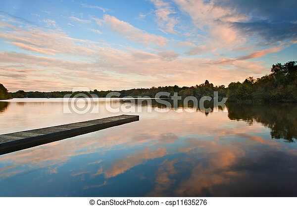 Beautiful sunset over Autumn Fall lake with crystal clear reflec - csp11635276
