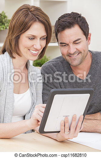 Happy Man & Woman Couple Using Tablet Computer at Home - csp11682810
