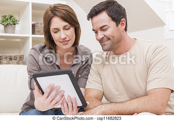 Happy Man & Woman Couple Using Tablet Computer at Home - csp11682823