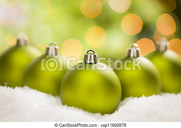 Green Christmas Ornaments on Snow Over an Abstract Background - csp11692878