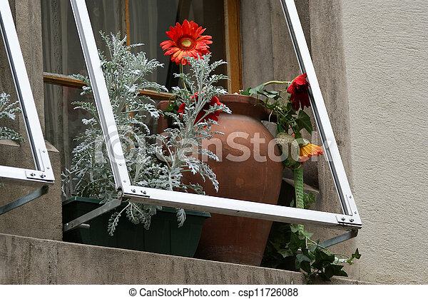 ceramic vase with flowers on the window sill - csp11726088
