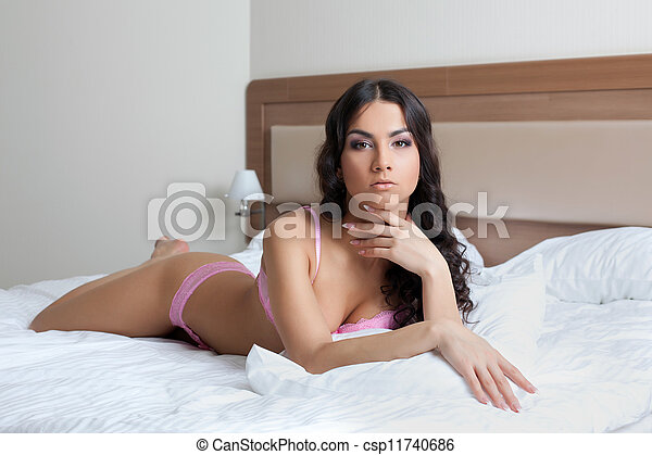 Sexy young brunette woman lying on bed - csp11740686