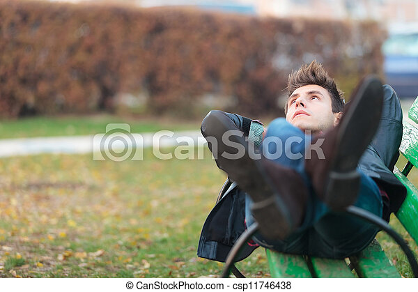 relaxed man on a bench in a park - csp11746438