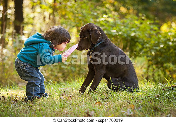 Young child playing fetch with dog - csp11760219