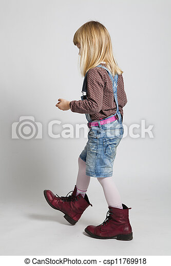 Young girl walking in adult sized boots - csp11769918