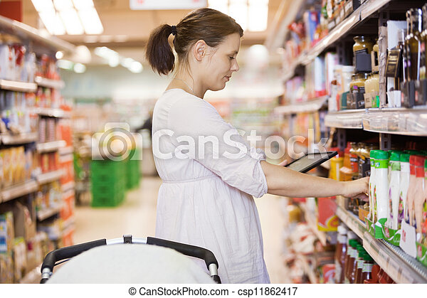 Mid Adult Woman Using Digital Tablet At Supermarket - csp11862417