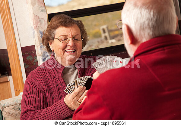 Happy Senior Adult Couple Playing Cards in Their Trailer RV - csp11895561
