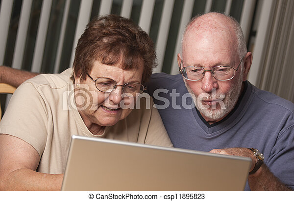 Smiling Senior Adult Couple Having Fun on the Computer - csp11895823