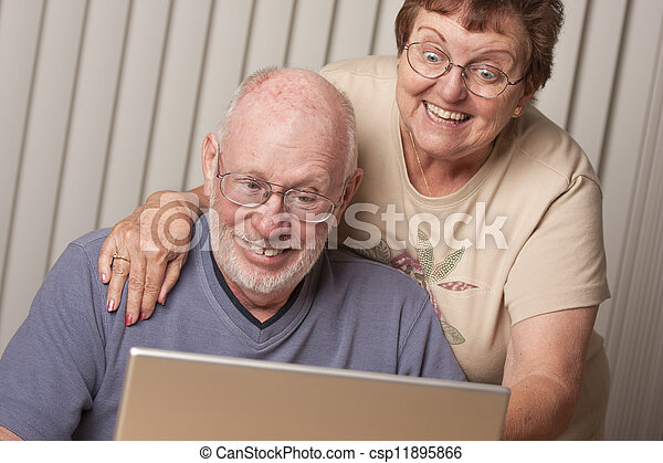 Smiling Senior Adult Couple Having Fun on the Computer - csp11895866