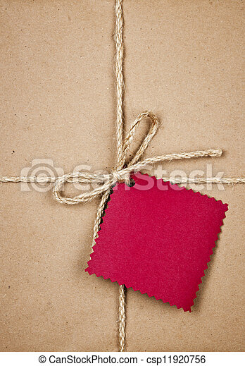 Gift with red tag in brown paper - csp11920756
