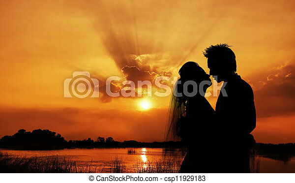 silhouette of a young bride and groom on Sunset background - csp11929183