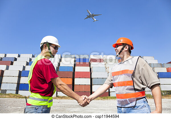 two happy workers handshaking before transportation containers - csp11944594