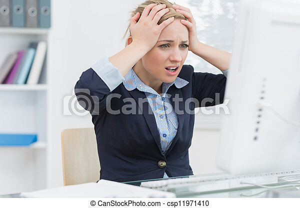 Frustrated business woman in front of computer at office desk - csp11971410
