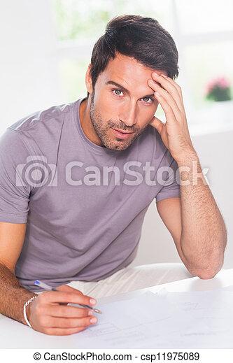 Man doing his accounting and looking at camera - csp11975089