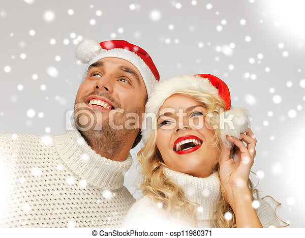 family couple in sweaters and santa\'s hats