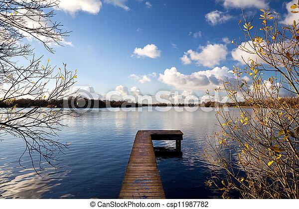 wooden pier on big lake in autumn - csp11987782