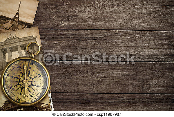 brass antique compass on table with old postcards and landmarks photographs - csp11987987