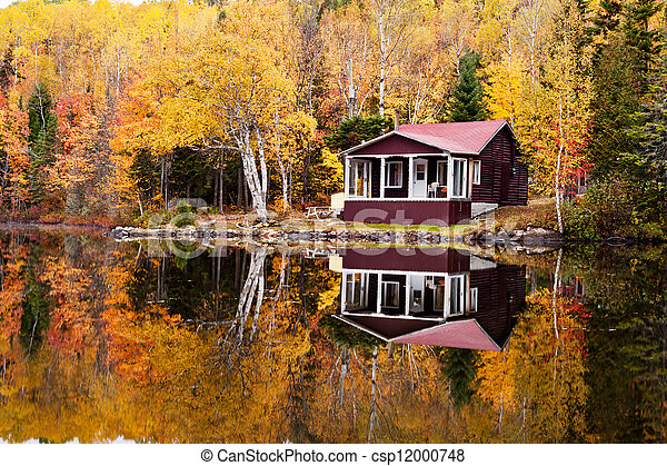 Reflections of a autumn forest and a house in a lake - csp12000748