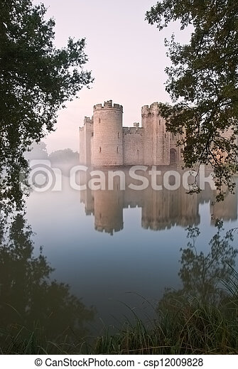Beautiful medieval castle and moat at sunrise with mist over moat and sunlight behind castle - csp12009828