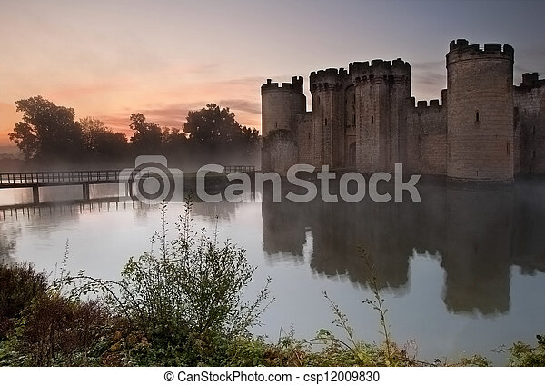 Beautiful medieval castle and moat at sunrise with mist over moat and sunlight behind castle - csp12009830