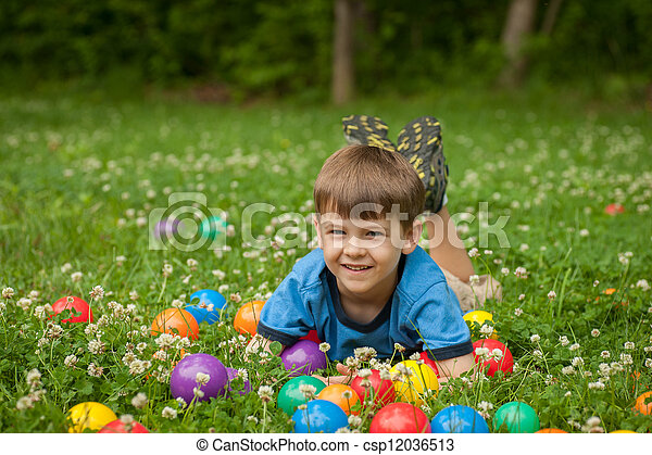 A five year old boy laies in the grass surrounded by colorful toy balls. The boy has expressions of fun and happiness. - csp12036513