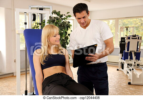 Attractive blonde woman and her trainer in a gym - csp12044408