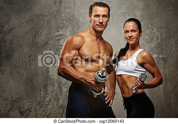 Athletic man and woman with a dumbbells. - csp12060143