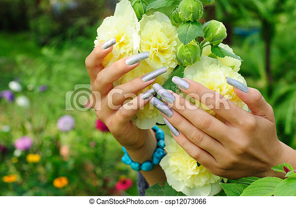 Manicure on real nails and yellow hollyhock flower - csp12073066