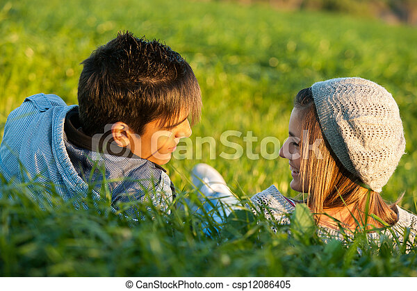 Couple laying in grass field at sunset. - csp12086405