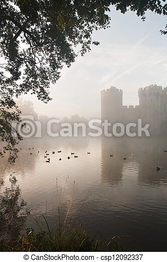 Beautiful medieval castle and moat at sunrise with mist over moat and sunlight behind castle - csp12092337