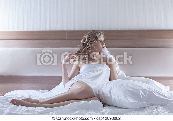 Sexy blonde woman sitting on bed - csp12098082