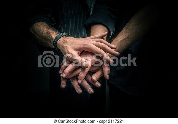 Group of young adults making a pile of hands - csp12117221