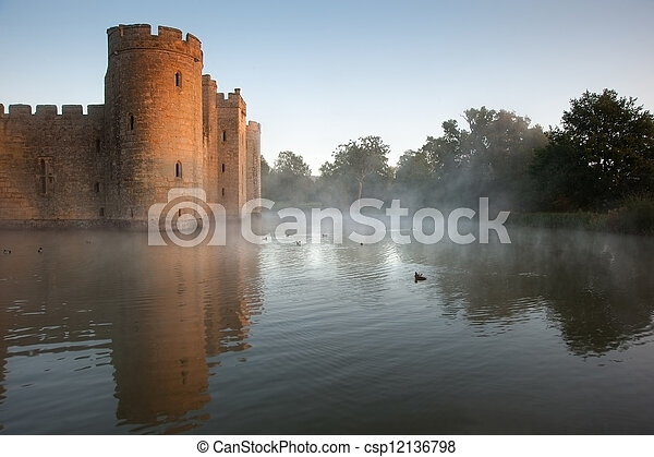 Beautiful medieval castle and moat at sunrise with mist over moat and sunlight behind castle - csp12136798