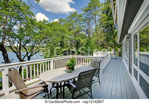 Large long balcony home exterior with table and chairs, lake view. - csp12142807