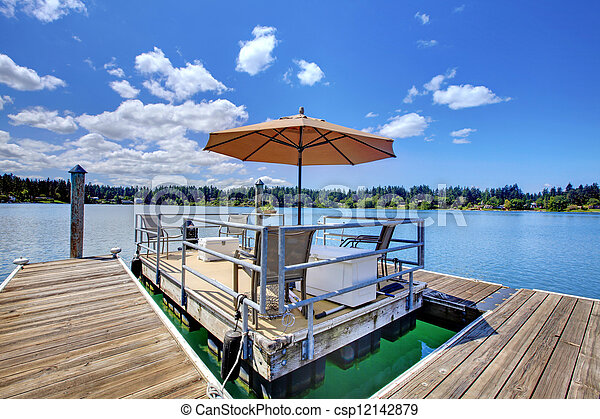 Lake with wood pier and private party raft. - csp12142879