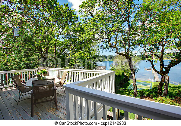 Large balcony home exterior with table and chairs, lake view. - csp12142933