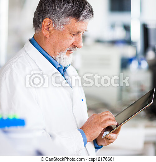 Senior doctor/scientist using his tablet computer at work - csp12176661