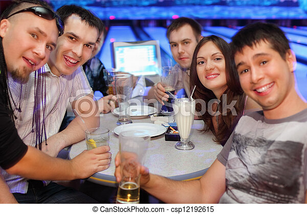 Happy friends sit at table and drink beer and cocktails in bowling; five men and one woman; focus on second man on left and woman  - csp12192615