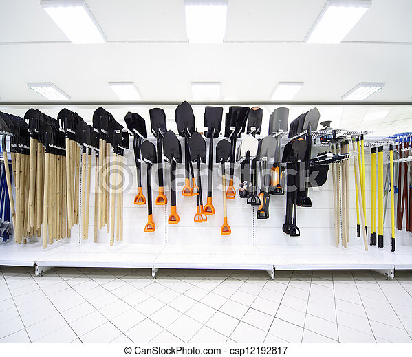 Shelves with variety of spade and other agricultural instruments inside large supermarket