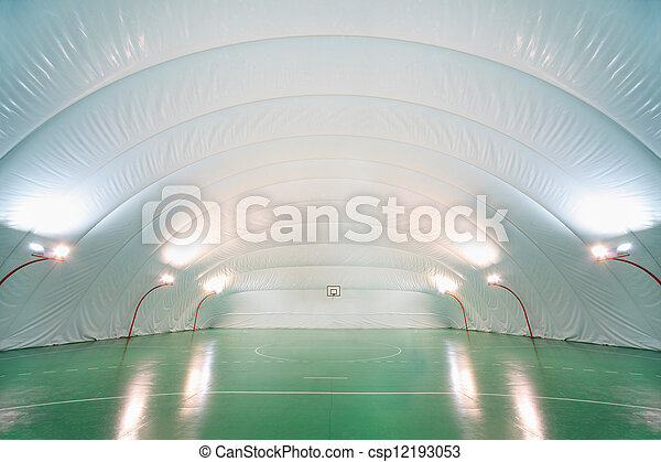 People train in indoor sports ground, plastic white ceiling and walls, green floor - csp12193053