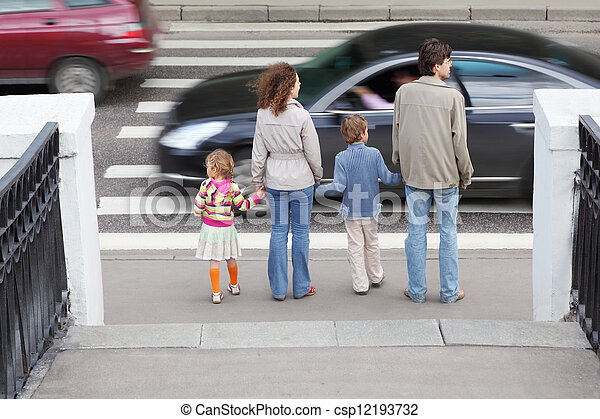 mother and father holds hand of little daughter and son and standing near pedestrian crossing, behind, two cars on road
