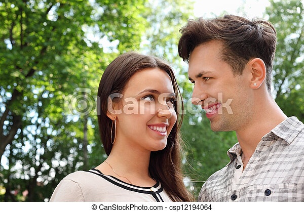 Happy man and woman stand in park and look at each other; green trees and sunny day; focus on girl - csp12194064