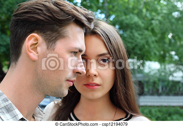 Beautiful pensive man and woman stand in park; green trees; focus on woman - csp12194079