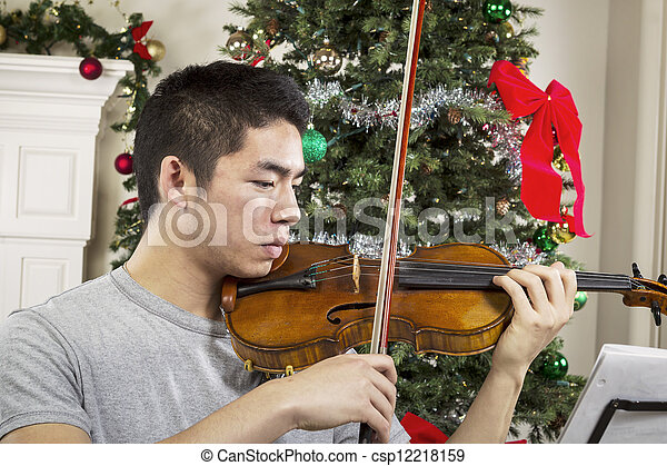 Young Adult Man Playing Music During the Holidays  - csp12218159