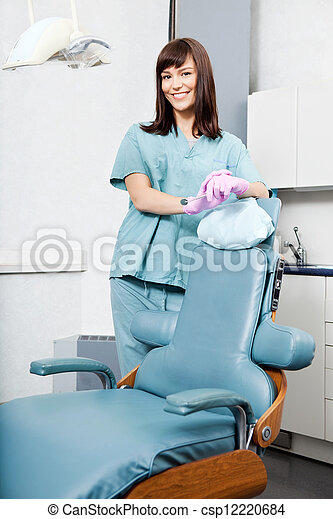 Smiling Female Dentist Standing By Dental Chair At Clinic - csp12220684