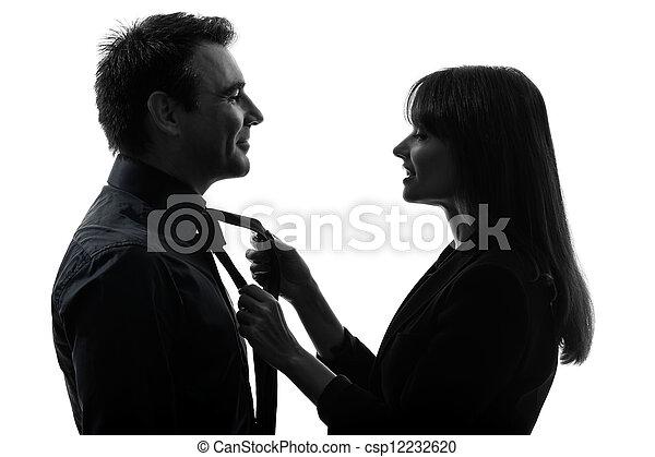 couple woman helping man tying silhouette - csp12232620